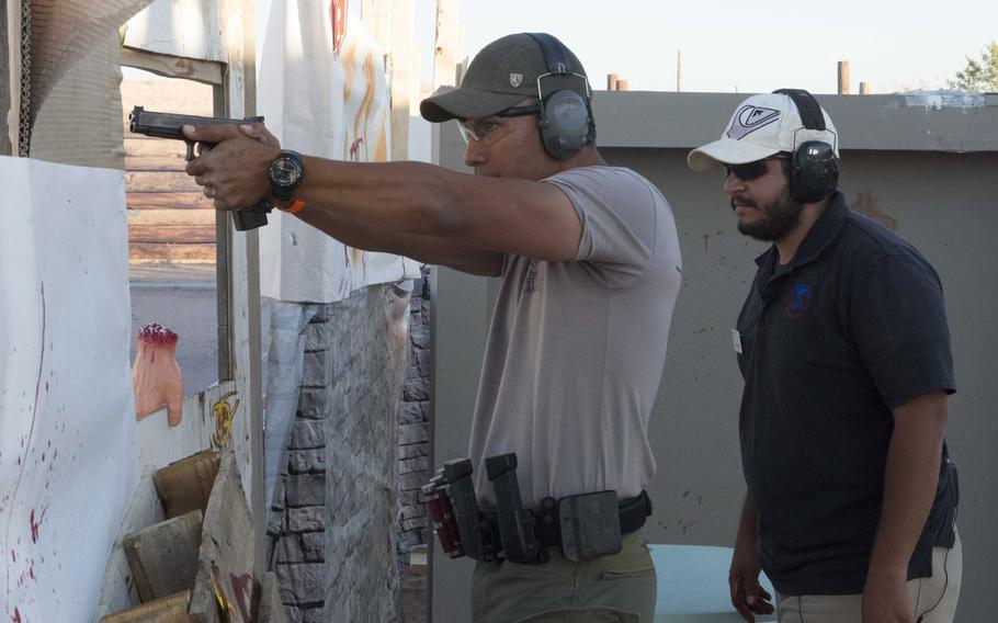 Ian Meyers of the U.S. Border Patrol engages paper targets while Israel Fornelli, a recreational aide with the Fort Bliss MWR, observes during the zombie shoot at the Rod and Gun Club at Fort Bliss, Texas, on Friday.