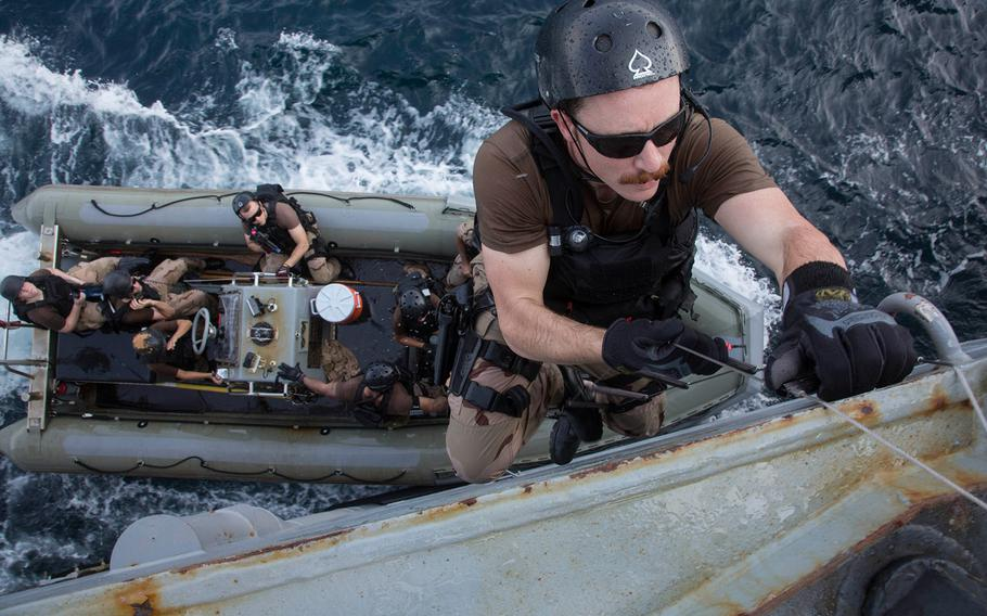 Ensign John Bozzelli climbs aboard the guided-missile destroyer USS Mason from a rigid hull inflatable boat.