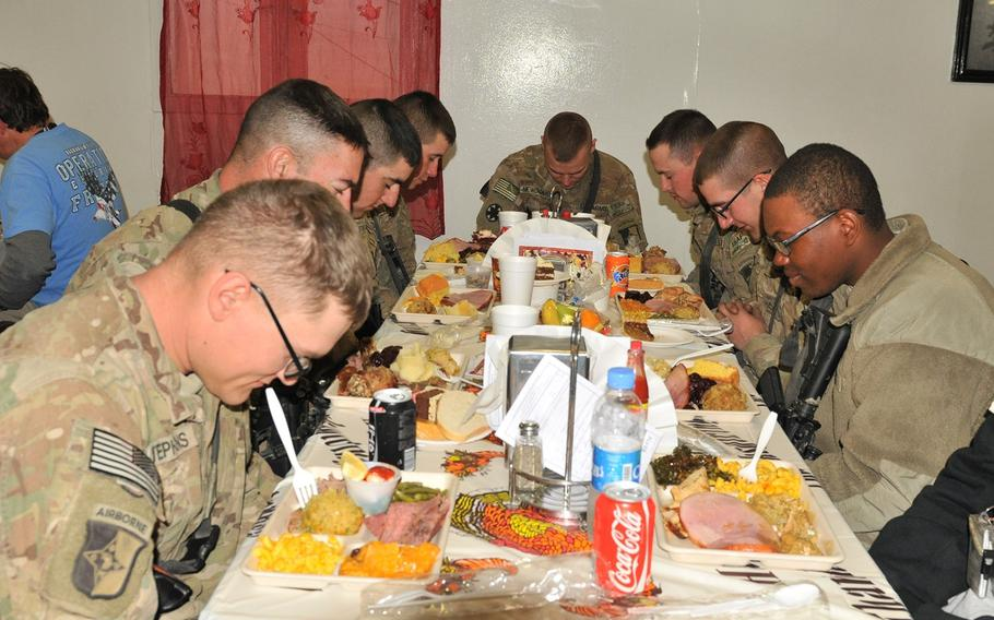 Task Force Lifeliner soldiers bow their heads and give thanks during Thanksgiving Day at the Koele Dining Facility, Nov. 28, 2013, at Bagram Air Field, Parwan province, Afghanistan. The soldiers had the opportunity to celebrate their holiday with a variety of traditional foods.