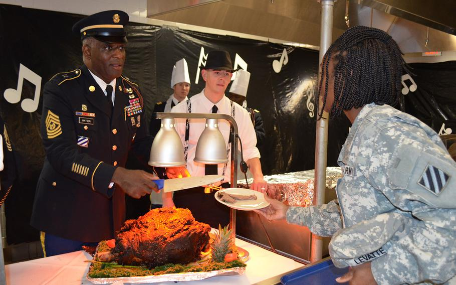 Command Sgt. Maj. Edd Watson, 3rd Infantry Division command sergeant major, serves Sgt. 1st Class Demeta Levatte, a 603rd Aviation Support Battalion soldier, a portion of her Thanksgiving lunch Nov. 27 at Hunter Army Air Field, Ga.