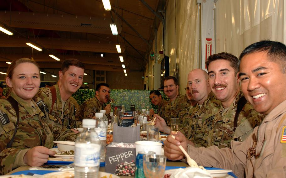 Airmen enjoy a Thanksgiving meal at the North Line Dining Facility at Kandahar Air Field, Afghanistan, on Nov. 28, 2013. Servicemembers were treated to traditional foods including turkey, stuffing, mashed potatoes, yams and cake.