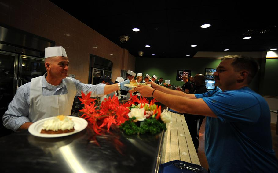 Navy Cmdr. Gordon Meek III helps serve Thanksgiving Day meal for junior members of his command in Okinawa on Nov. 28, 2013.