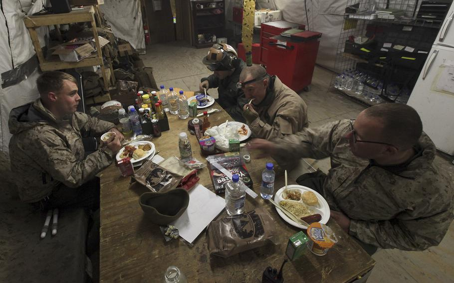 The early morning shift of workers at Marine Light Attack Helicopter Squadron 369 eat a Thanksgiving breakfast together during a break in their shift Nov. 28, 2013 at Camp Leatherneck, Afghanistan.
