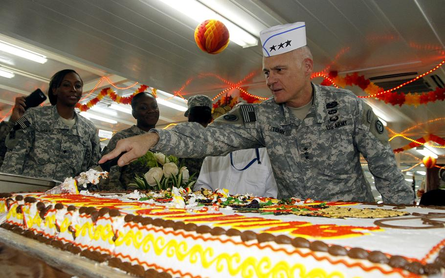 Lt. Gen. James L. Terry, commanding general, U.S. Army Central Command, cuts a cake during Thanksgiving lunch at Camp Buehring in Kuwait.