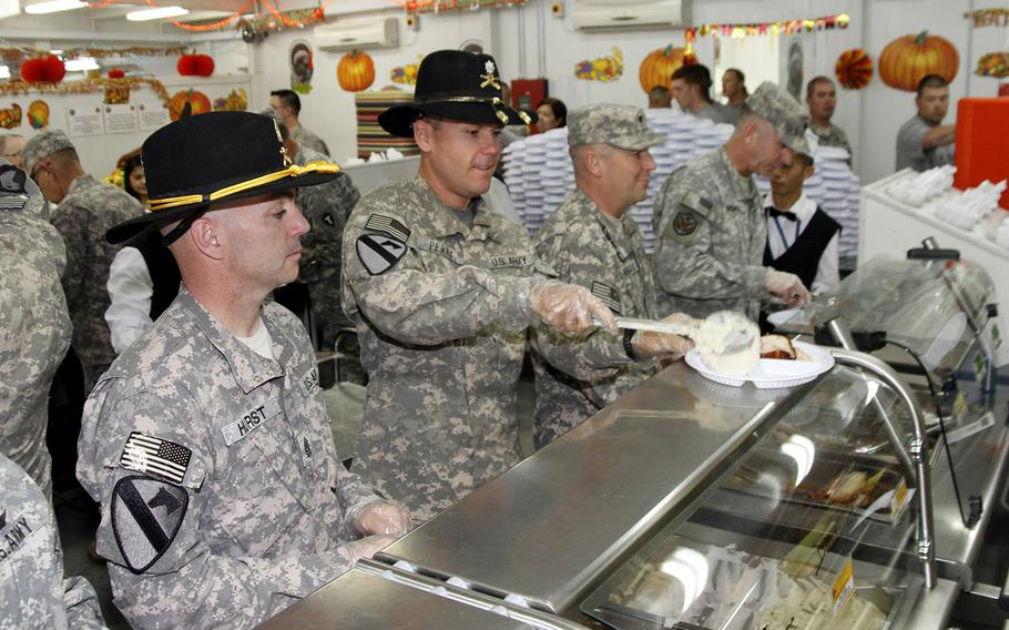 Command Sgt. Maj. Zacchaeus Hurst, left, and Lt. Col. Henry Perry, right, of the 4-227th Attack-Reconnaisance Battalion, 1st Cavalry Division serve Thanksgiving lunch to soldiers at Camp Buehring in Kuwait.