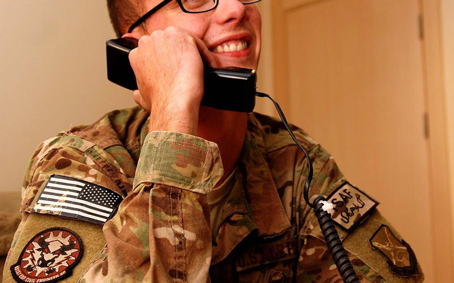 Staff Sgt. Dustin Hawkins, 451st Expeditionary Civil Engineer Squadron, Kandahar Airfield, Afghanistan, talks to President Barack Obama on the phone Nov. 28, 2013. The president thanked Hawkins for his service and talked football with him. Hawkins is deployed from Mountain Home Air Force Base, Idaho.