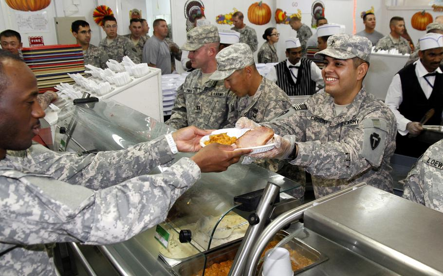 Maj. Guillermo Cardona of the 449th Aviation Support Battalion, chaplain, serves Thanksgiving lunch to soldiers at Camp Buehring in Kuwait.