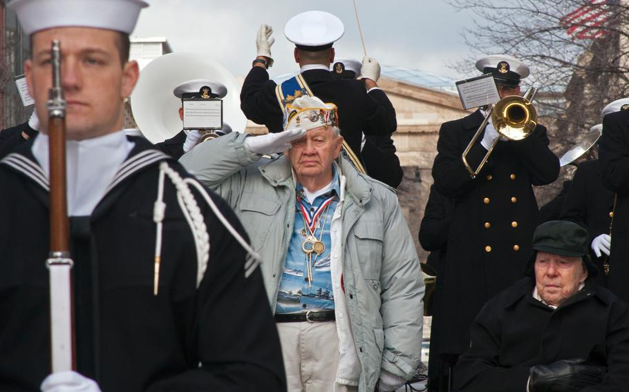 Pearl Harbor survivor STC Howard Snell stands to salute the U.S. Navy Color Guard during the Pearl Harbor Remembrance Day on Dec. 7, 2013. To the right of Snell is another Pearl Harbor survivor, Major Albert Grasselli, who was stationed at Ewa Beach Marine Airfield.