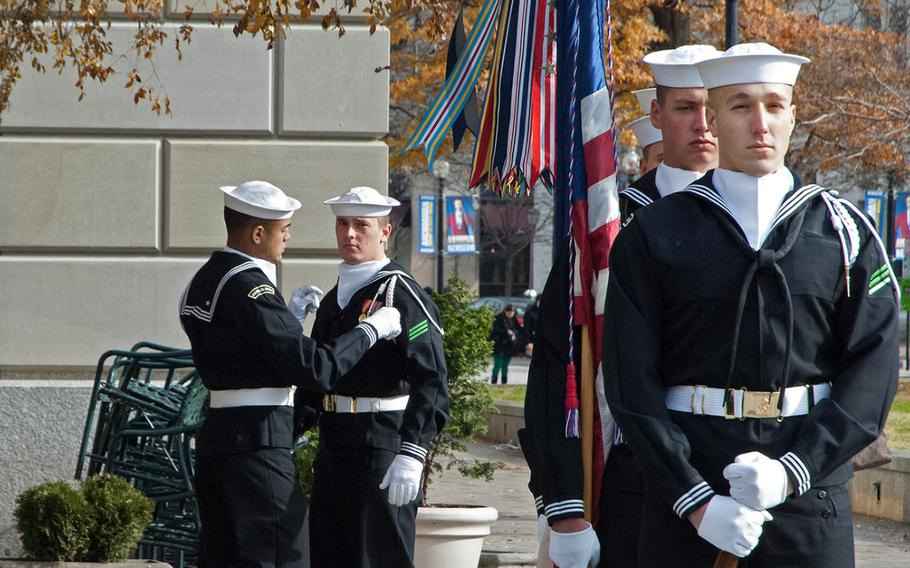 A sailor helps another sailor out before they participate in the Pearl Harbor Remembrance Day at the U.S. Navy Memorial in Washington, D.C. on Dec. 7, 2013.