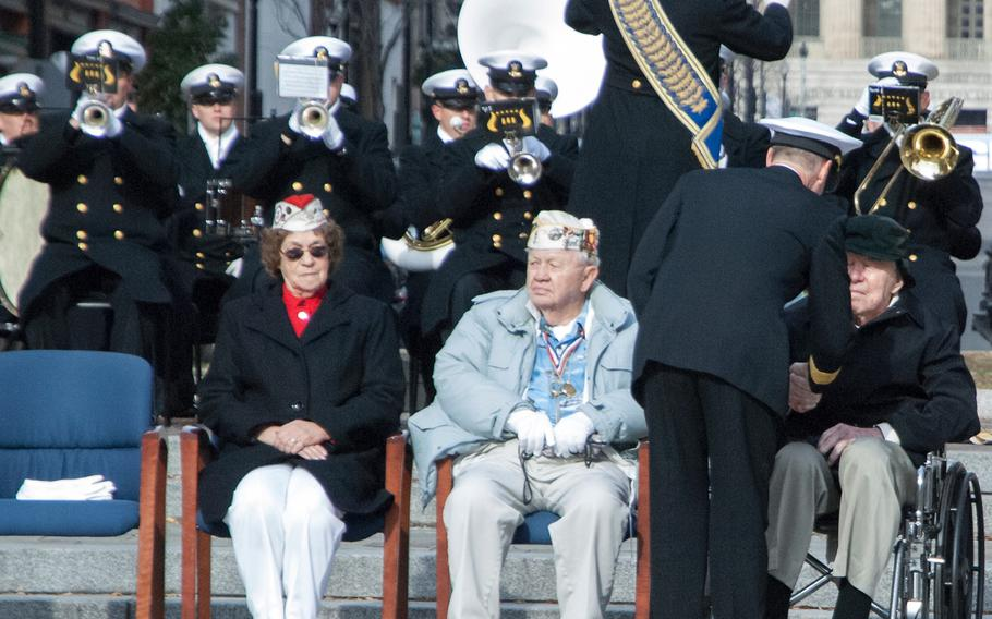 Pearl Harbor survivors Howard Snell, sitting left in the grey jacket, and Major Albert Grasselli receive coins during the Pearl Harbor Remembrance Day on Dec. 7, 2013, at the U.S. Navy Memorial in Washington, D.C.