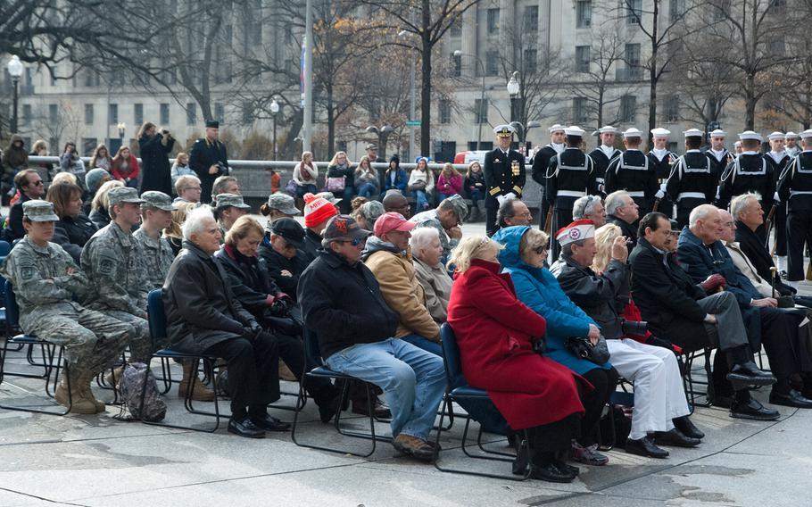 People huddle in their coats during the Pearl Harbor Remembrance Day at the U.S. Navy Memorial in Washington, D.C., on Dec. 7, 2013.