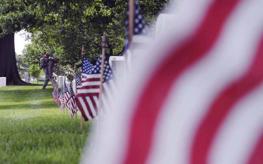 """Staff Sgt. Francisco Armenta plants flags at graves at Arlington National Cemetery on May 22, 2014 as part of a """"Flags In"""" ceremony to honor fallen troops for Memorial Day."""