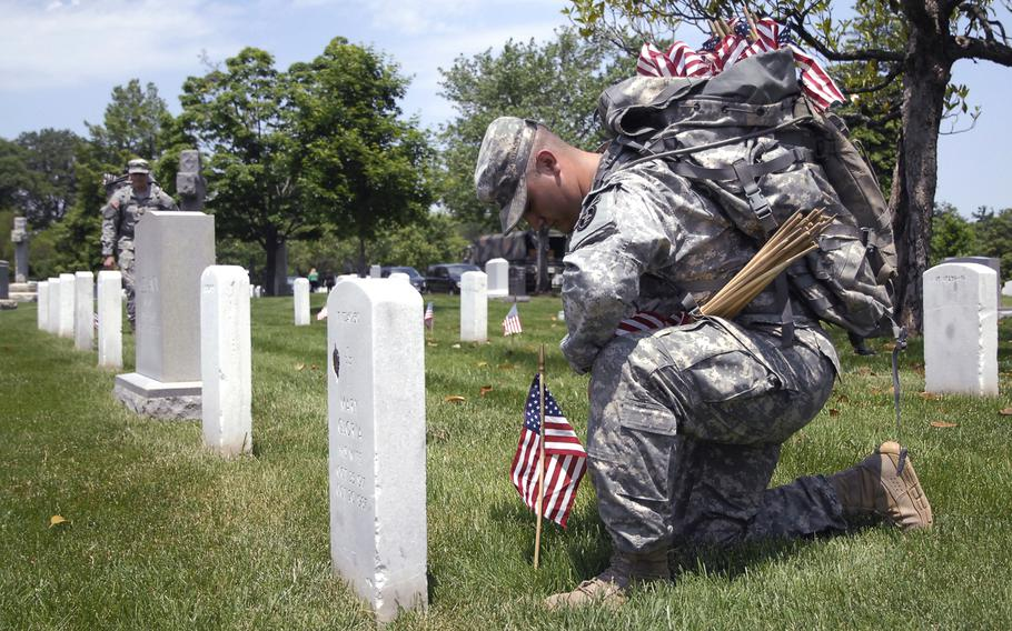 """A soldier plants flags at graves at Arlington National Cemetery on May 22, 2014 as part of a """"Flags In"""" ceremony to honor fallen troops for Memorial Day."""