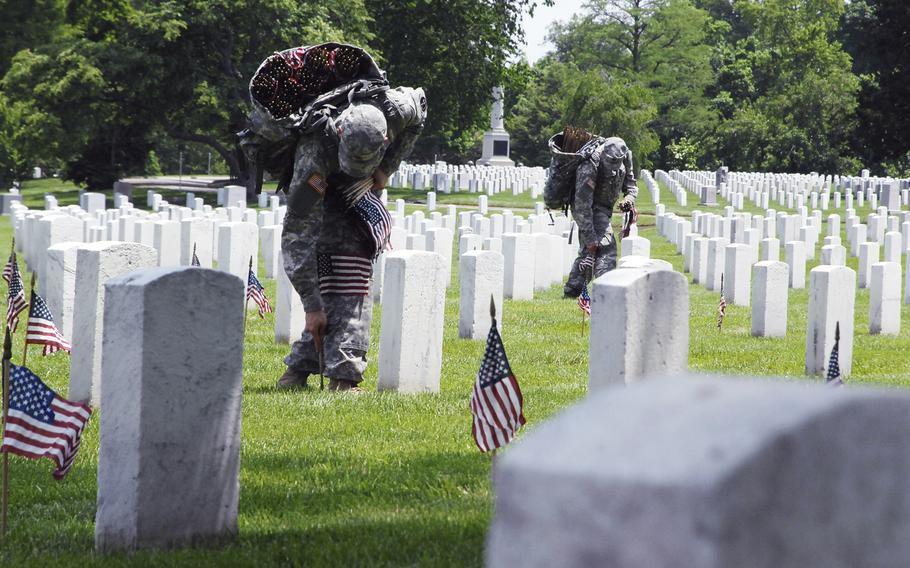 """Soldiers plant flags at graves at Arlington National Cemetery on May 22, 2014 as part of a """"Flags In"""" ceremony to honor fallen troops for Memorial Day."""