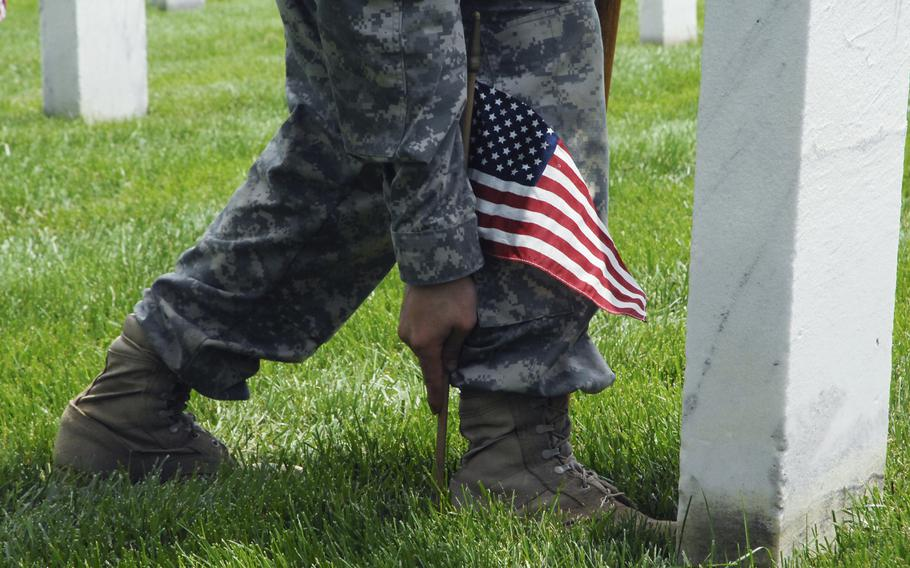 """A soldier plants flags at graves at Arlington National Cemetery on May 22, 2014 as part of a """"Flags In"""" ceremony to honor fallen troops for Memorial Day. Soldiers would place their boot against a gravestone and plant a flag at the heel to achieve a uniform look across the cemetery."""
