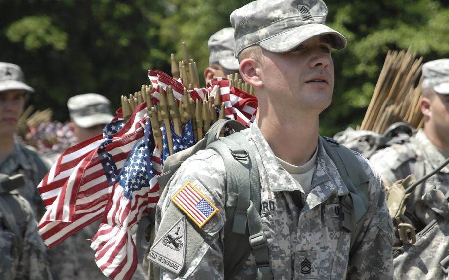 """Soldiers head out to plant flags at graves at a """"Flags In"""" ceremony at Arlington National Cemetery on May 22, 2014, to honor fallen troops for Memorial Day."""