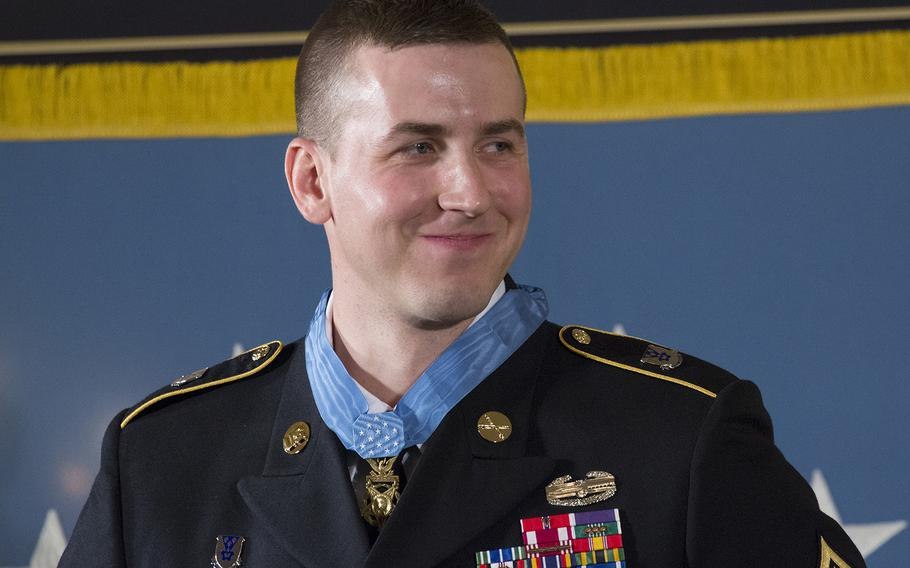 Former Army Staff Sgt. Ryan Pitts smiles as President Barack Obama speaks during the Medal of Honor ceremony at the White House, July 21, 2014.