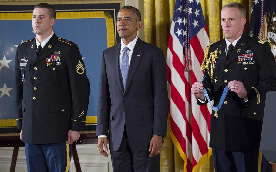 Former Army Staff Sgt. Ryan Pitts, Pesident Barack Obama and a military aide listen as Pitt's Medal of Honor citation is read during the ceremony for  at the White House, July 21, 2014.