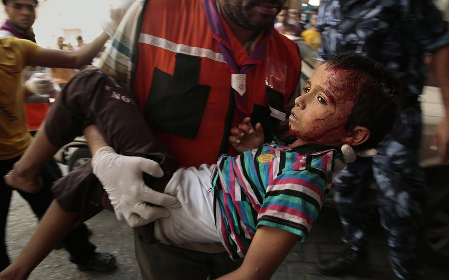 A boy who was wounded at the market in Shujayea, in Gaza City, is rushed to Shifa Hospital on Wednesday, July 30, 2014.