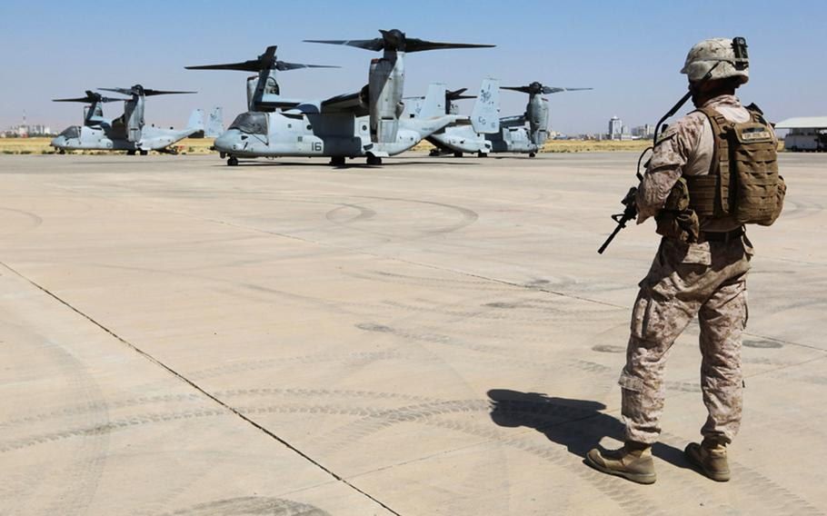 A U.S. Marine guards 3 MV-22 Osprey aircraft during a humanitarian assessment mission in support of displaced Iraqi civilians trapped on Sinjar Mountain, Aug. 13, 2014.