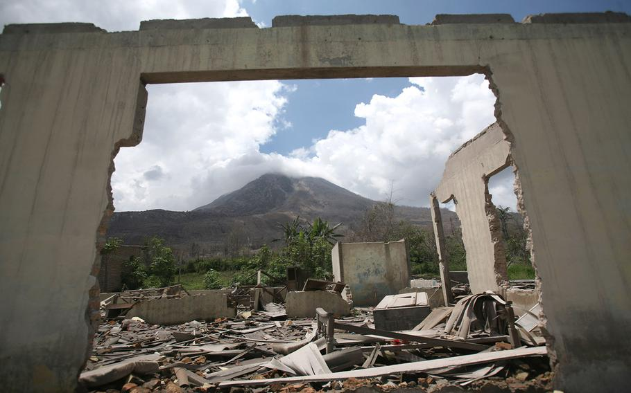 Mount Sinabung is framed by a crumbling building in the abandoned village of Simacem village, North Sumatra, Indonesia, on Oct. 17, 2014. The village was abandoned after its people were evacuated following the eruption of the volcano. Sinabung, among about 130 active volcanoes in Indonesia, has sporadically erupted since 2010 after being dormant for 400 years. More than 22,000 people were evacuated from the area around the 8,530-foot volcano after the eruptions earlier this year that killed at least 16 people. Most have returned home, but about 4,700 remain in evacuation centers.