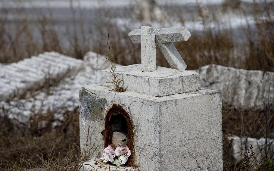 In this May 7, 2013 photo, a cross lies broken on a tomb in the abandoned town of Epecuen, Argentina. This town was once home to 1,500 residents, but they were forced to leave in 1985 when heavy rains made the nearby lake overrun its banks and submerged the town beneath almost 30 feet of water. The town was never rebuilt as the water started to recede.