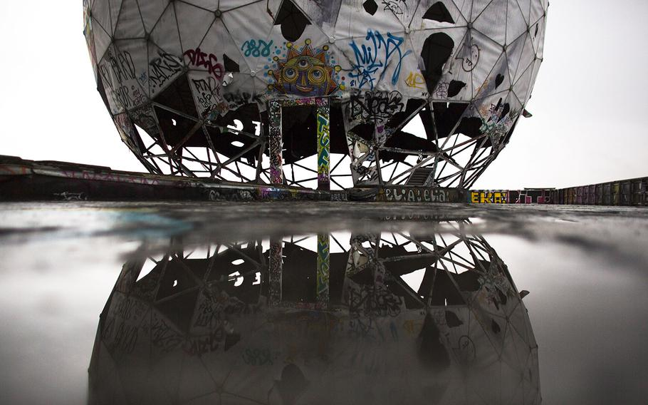 In this Oct. 16, 2014 photo, the ruin of a vandalized, golf ball-shaped cover for antennas of the abandoned former listening station of the United States National Security Agency, at the Teufelsberg (Devil's Mountain) is reflected in a puddle in Berlin. The listening station, which was active until the early '90s, is now used by graffiti artists and can be visited only with guided tours.
