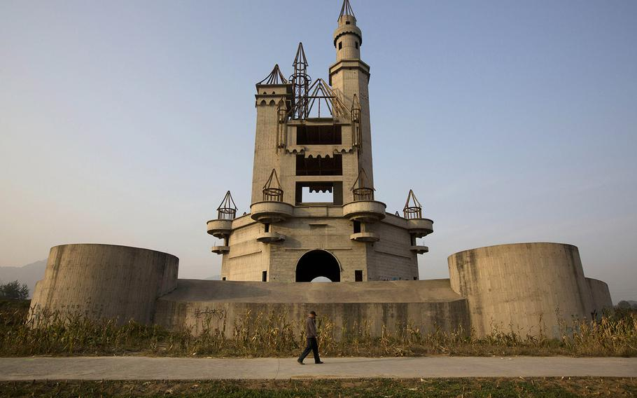 In this Oct. 18, 2014, photo, a man walks past the shell of a castle-like building that was once destined to be part of Asia's biggest amusement park in Beijing, China. Work halted on the project in 1998 due to financial problems and the site has been left as it is until 2013 when developers demolished other parts of the massive park for redevelopment. The castle-like building however remains untouched and a reminder of better times in that part of Beijing's periphery.