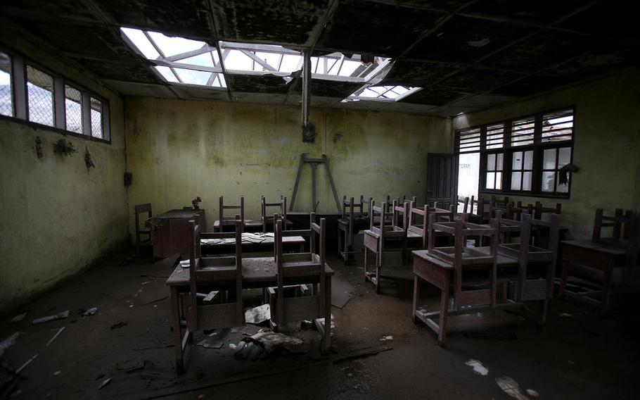 In this Oct 17, 2014, photo, chairs rest on tables in an empty classroom at an elementary school in the abandoned village of Simacem, North Sumatra, Indonesia. The village was abandoned after its people were evacuated following the eruption of Mount Sinabung.