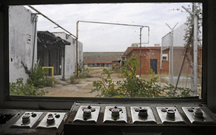 In this Oct. 23, 2014, photo, buttons that used to open and close many of the gates sit with a view of some of the out buildings at the abandoned Central State Farm prison in Sugar Land, Texas. The unit was closed down three years ago.