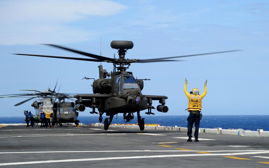 An Army AH-64E Apache Guardian helicopter takes off from the amphibious assault ship USS Peleliu in the Pacific Ocean during RIMPAC 2014 exercises.