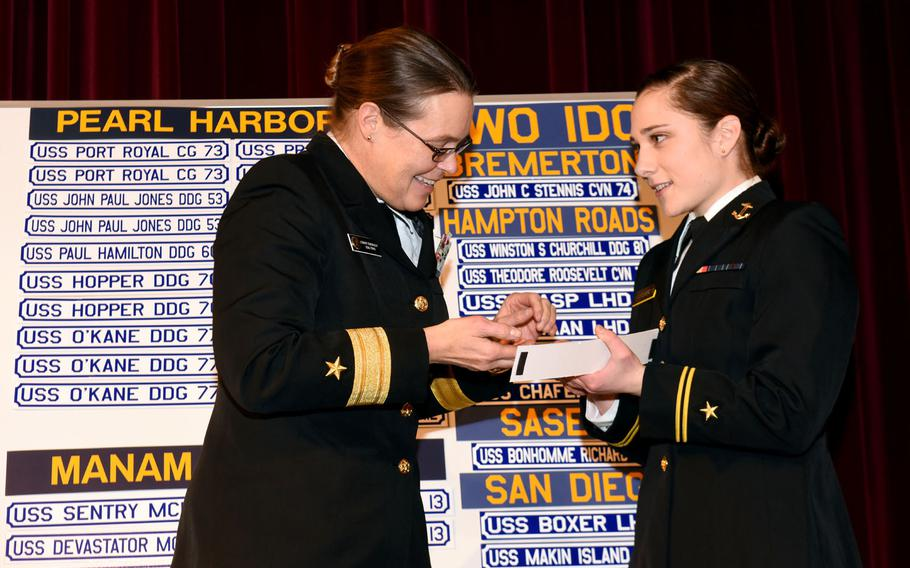 Rear Adm. Cynthia M. Thebaud, commander of Expeditionary Strike Group 2, presents her Surface Warfare Officer pin to U.S. Naval Academy Midshipman 1st Class Lily Van Steenberg during Ship Selection Night in Mahan Hall on Jan. 29, 2015. Ship Selection is the culmination of the service assignment process for Naval Academy midshipmen assigned to serve as Navy Surface Warfare Officers. Upon reporting to their first ship after graduation and commissioning, they will be in charge of any number of shipboard operations and activities while at sea.