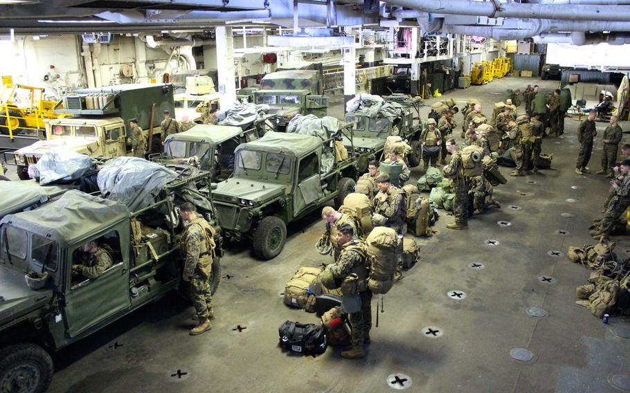 Marines with Battalion Landing Team 2nd Battalion, 1st Marine Regiment, 11th Marine Expeditionary Unit, prepare to load their vehicles onto a landing craft air cushion to return to Camp Pendleton, Calif., from the USS Makin Island. The unit was deployed on the ships of the Makin Island Amphibious Ready Group for seven months. Photo by