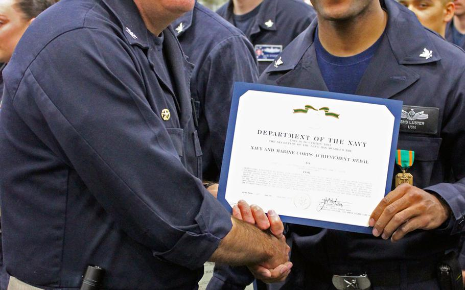 Capt. Jon Rodgers, captain of the USS Makin Island, presents awards to sailors and Marines aboard the ship on Feb. 24, 2015, as the Makin Island Amphibious Ready Group returned to San Diego from a seven-month deployment.