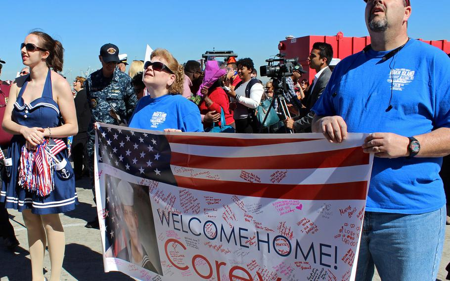 Families held signs as they kept an eye out for their sailors at Naval Base San Diego. The USS Makin Island, USS San Diego and USS Comstock -- all part of the Makin Island Amphibious Ready Group -- returned on Feb. 25, 2015, from a seven-month deployment.