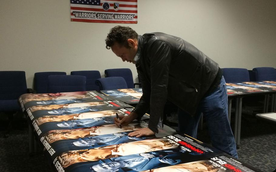 """Actor Vince Vaughn signs posters from his new movie, """"Unfinished Business,"""" for airmen and their families at Edwards Air Force Base, Calif., on Saturday. Vaughn visited the base to screen the movie for troops."""