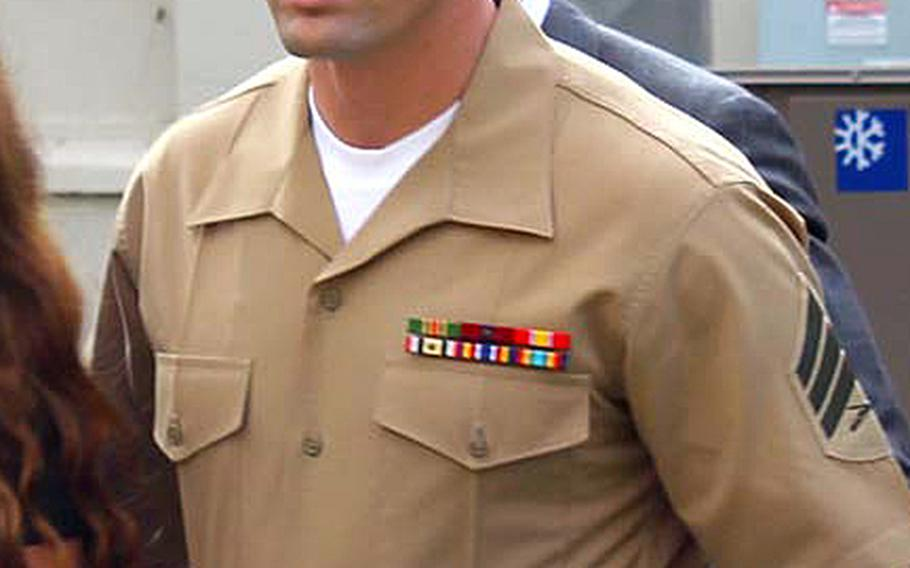 Sgt. Lawrence G. Hutchins III walks to a court room for a hearing at Camp Pendleton, Calif., on Aug. 14, 2014.