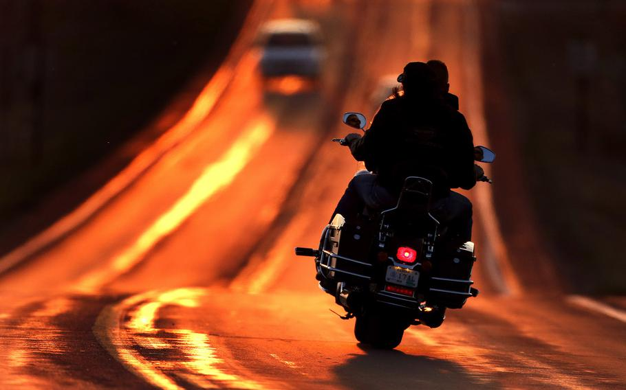 A motorcyclist takes advantage of warmer weather to travel on a highway illuminated by the setting sun on the first full day of spring on March 21, 2015, in Lawrence, Kan.