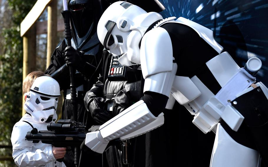 Grant Tunnell, 5, left, dressed as a mini-Stormtrooper, borrows a blaster rifle from a grown-up Stormtrooper on Star Wars Character Day at the Knoxville Zoo on March 21, 2015, in Knoxville, Tenn. Grant visited with parents Steve and Heather of Greenville, Tenn. on a day when the zoo offered free admission to children dressed as Star Wars characters.