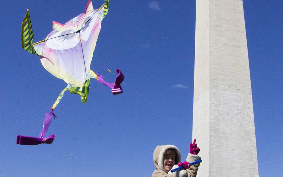 Six-year-old Elee Cie of Silver Spring, Md. guides her kite aloft during the fifth annual Blossom Kite Festival in Washington, D.C., March 28, 2015.
