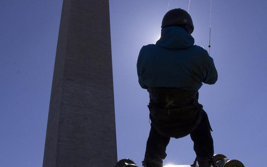 Landboarder Lon Phan of Silver Spring, Md., is silhouetted against the sun as takes to the air in front of the Washington Monument in the early minutes of the fifth annual Blossom Kite Festival in Washington, D.C., March 28, 2015.
