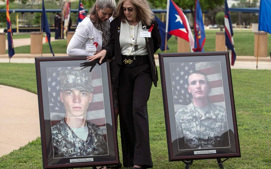 Teena Nemelka, left, mother of Pfc. Aaron Nemelka, left picture, and Sheryll Pearson, right, mother of Pfc. Michael Pearson, right picture, visit one another, on April 10, 2015, at Fort Hood, Texas, before receiving the Purple Heart for their sons who were killed during the attack.