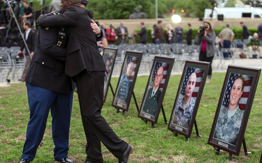 Purple Heart recipients Pfc. James Armstrong, left, and Chief Warrant Officer 2 Christopher Royal hug as they look at pictures of co-workers who were killed in the 2009 Fort Hood shooting, prior to a ceremony on April 10, 2015, at Fort Hood, Texas.