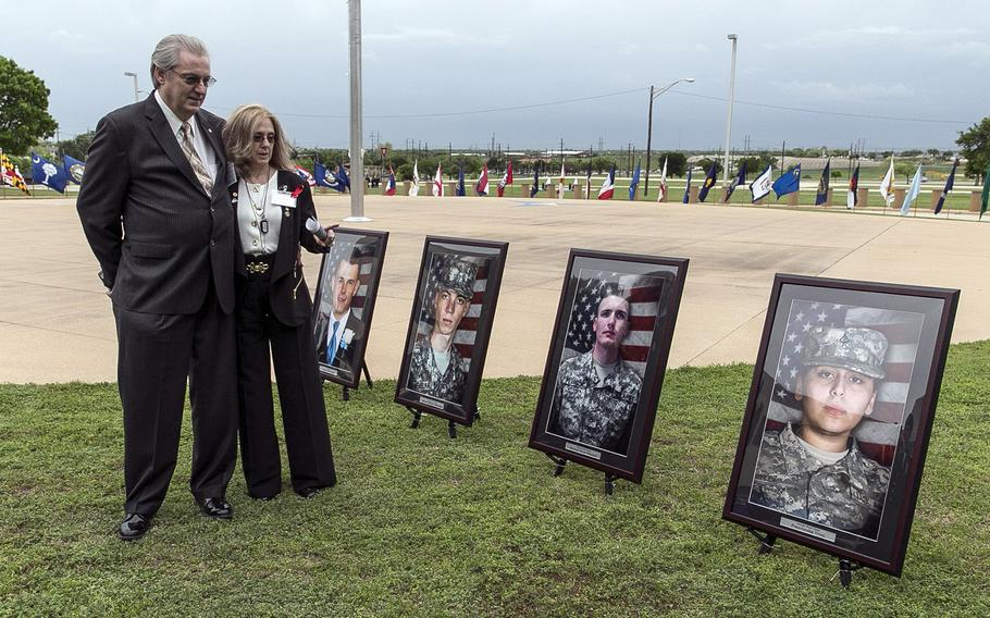 Jeffrey and Sheryll Pearson, parents of Pfc. Michael Pearson, second picture from right, visit in front of his picture prior to a Purple Heart ceremony held at Fort Hood, Texas, on April 10, 2015.