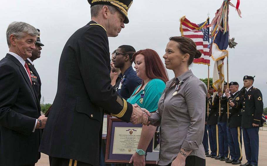 Secretary of the Army, John McHugh, far left, looks on as Lt. Gen. Sean B. MacFarland, center, shakes the hand of Defense of Freedom Medal recipient Kimberly Munley, who was wounded in the 2009 Fort Hood Shooting.