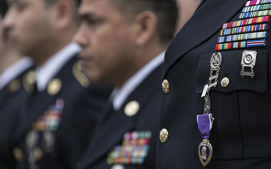 A ceremonial Purple Heart is clipped to the chest of Sgt. Alonzo Lunsford, Jr., during a Purple Heart ceremony held at Fort Hood, Texas, on April 10, 2015. Survivors and family members of those killed during the attack by Maj. Nidal Hasan in the 2009 Fort Hood shooting were awarded 44 medals, Purple Heart for soldiers and Defense of Freedom Medals for civilians.