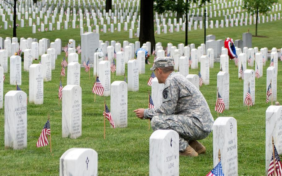 Staff Sgt. Oliver Moore visits the grave of Sgt. 1st Class James Scott Ochsner, killed in Afghanistan in 2005, during the Flags-In at Arlington National Cemetery in Arlington, Va., on Thursday, May 21, 2015.