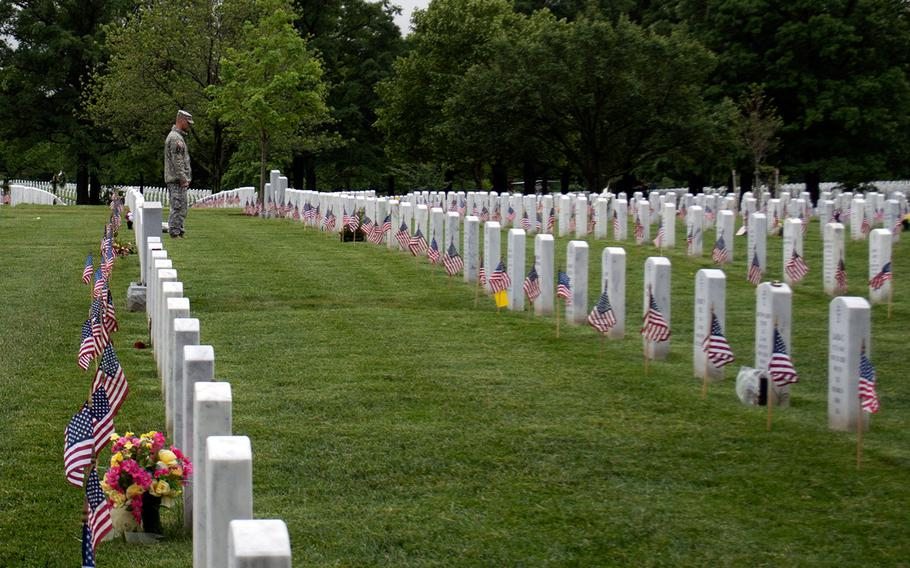 A member of the Old Guard pauses at a headstone during the Flags-In at Arlington National Cemetery on May 21, 2015, in Arlington, Va.