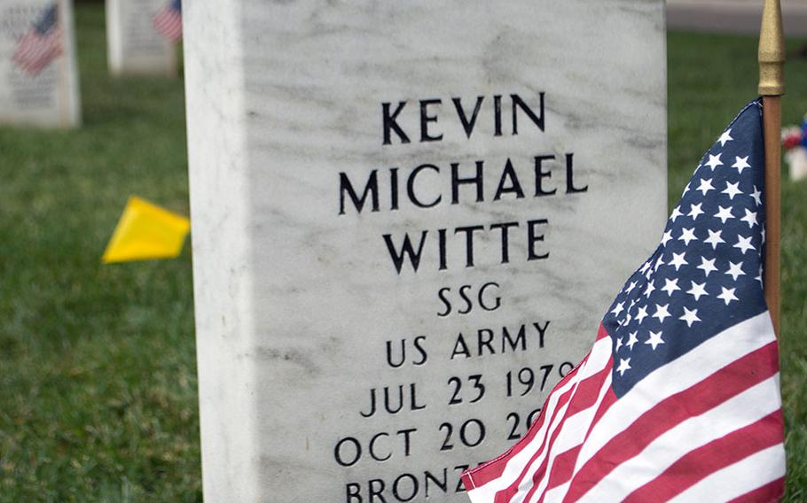 Silver airborne wings rest atop the grave of Staff Sgt. Kevin Michael Witte, placed there by his best friend, Staff Sgt. Oliver Moore, along with the American flag, during the Flags-In at Arlington National Cemetery on May 21, 2015, in Arlington, Va.