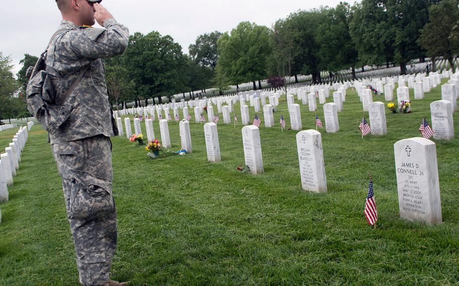 Spc. Nicholas Connell salutes his father, Sgt. 1st Class James D. Connell Jr., who was killed in action in 2007 in Iraq, during the Flags-In at Arlington National Cemetery on May 21, 2015, in Arlington, Va.